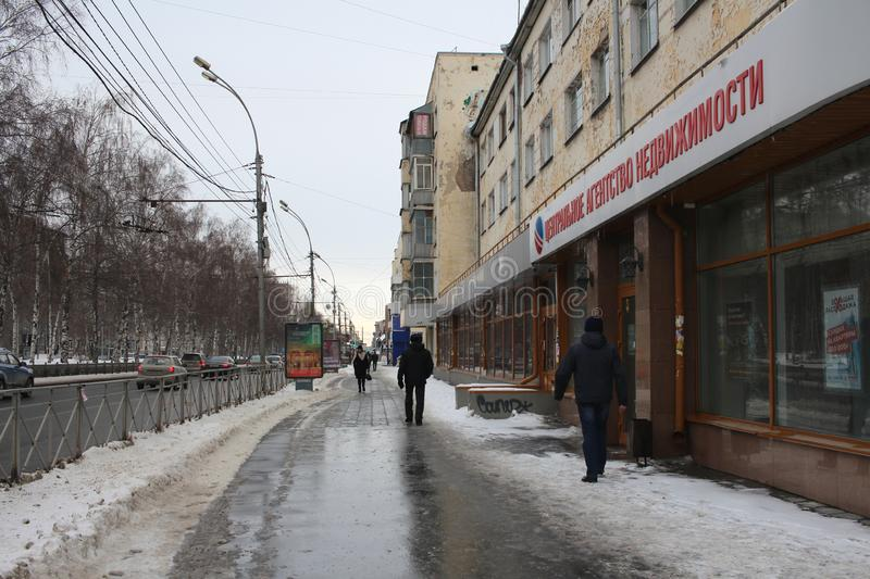 Russia, Novosibirsk, March 8, 2019: people walk in the spring on the melted snow on the sidewalk on the street in the city stock photography