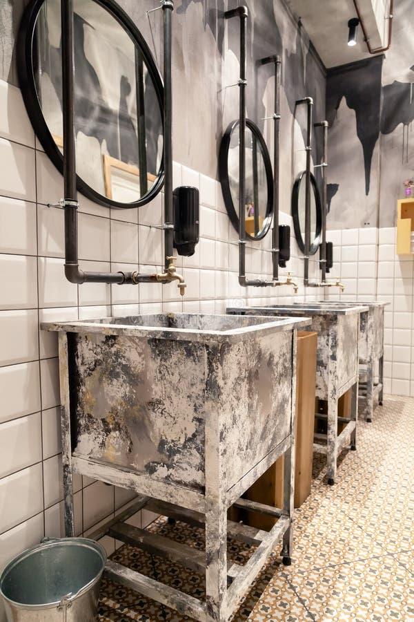 Russia Novosibirsk 2018-11-18 Modern interior of restaurant loft style toilet, square concrete sinks, copper faucet, black stock photography