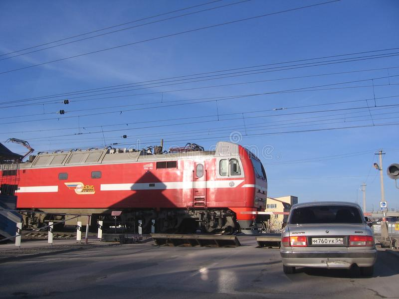 Russia, Novosibirsk, October 14, 2012: closed railway crossing with raised barriers passing locomotive car stopped misses train. Closed railway crossing with royalty free stock photography