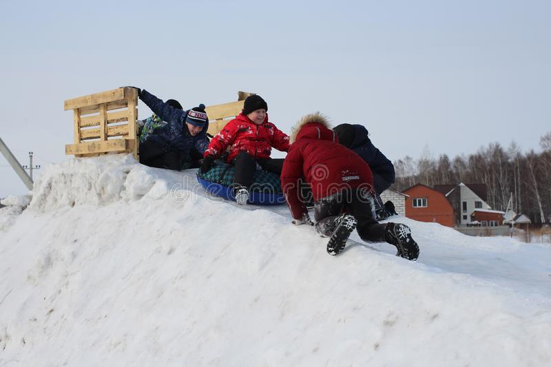 Young children joyfully ride with an ice slide in winter play on the street royalty free stock image