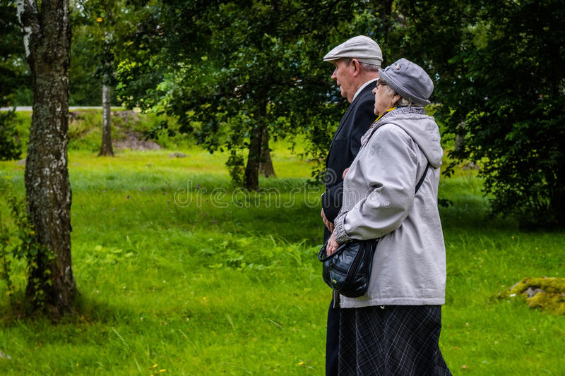 Russia, Priozersk, August 2016: An elderly couple together goes under the arm on the wooden walkway. Russia, Priozersk, August 2016 An elderly couple together stock photography