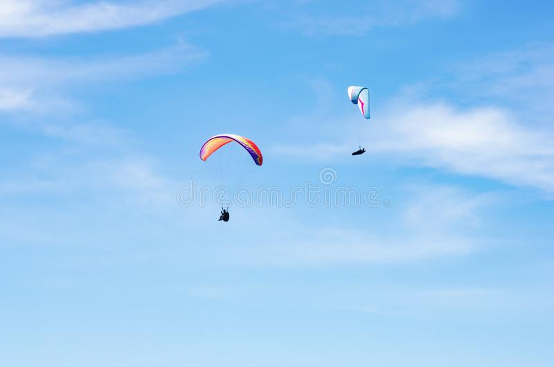 Two paragliders against the sky stock photo