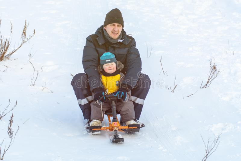 Russia, Ryazan 05 Jan 2019: happy man sliding down hill on snow tubes over winter natural background stock images