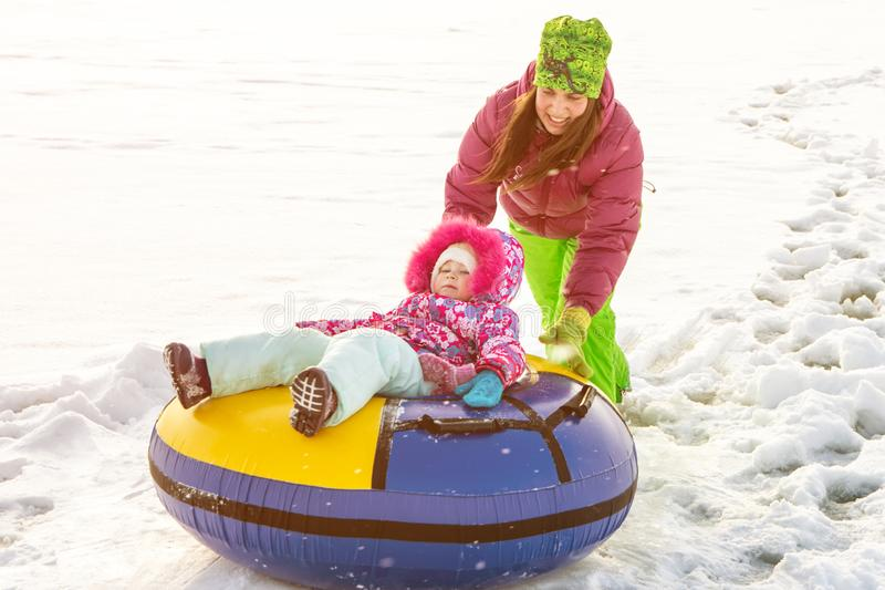 Russia, Ryazan 05 Jan 2019: happy woman with his family sliding down hill on snow tubes over winter natural background stock photo
