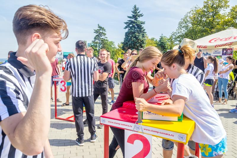 Arm wrestling among girls on the Volga River Embankment on a sunny summer day. Russia, Samara, August, 2018: arm wrestling among girls on the Volga River royalty free stock photography