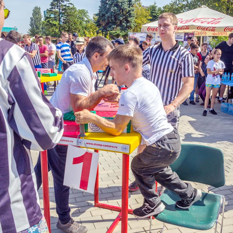 Arm wrestling among men with disabilities on the Volga River Embankment on a sunny summer day. Russia, Samara, August, 2018: Arm wrestling among men with royalty free stock photo