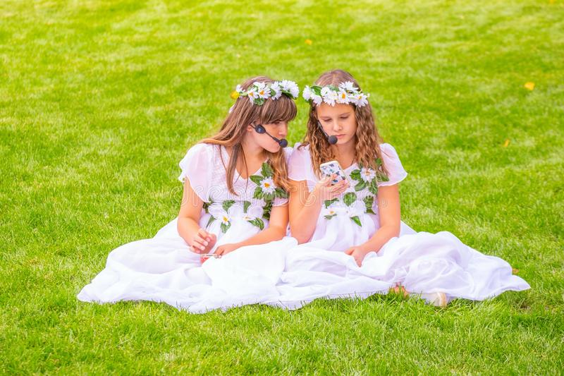 Two girls in white dresses decorated with flowers, with smartphones sitting on the grass. stock photos