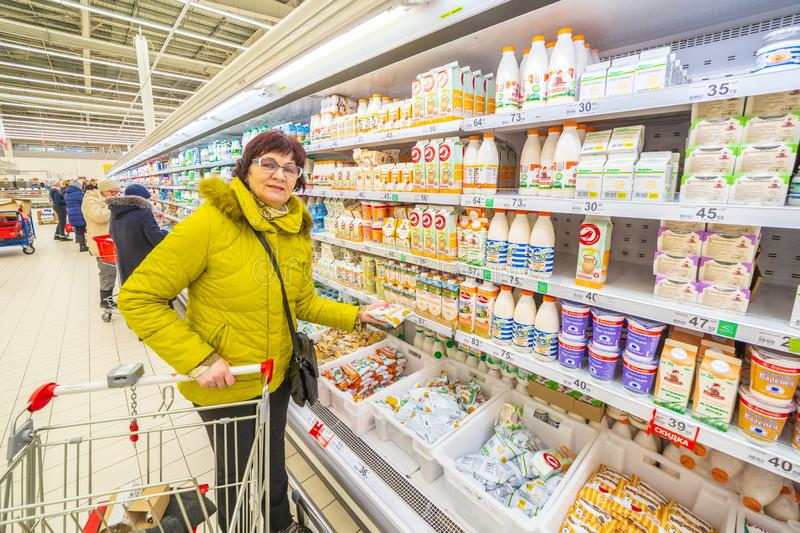 A beautiful mature woman chooses dairy products in the supermarket. stock image
