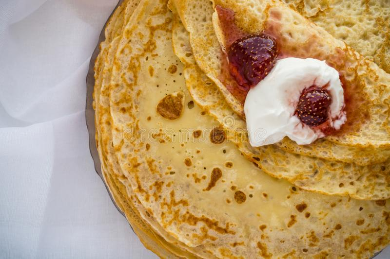 Russia, Severodvinsk, a stack of homemade Russian pancakes with sour cream and strawberry jam, flat lay stock image
