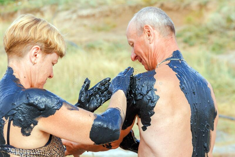 A mature married couple smears each other with curative mud. Russia, Sol-Iletsk, August 2016: a mature married couple smears each other with curative mud. Summer stock photos