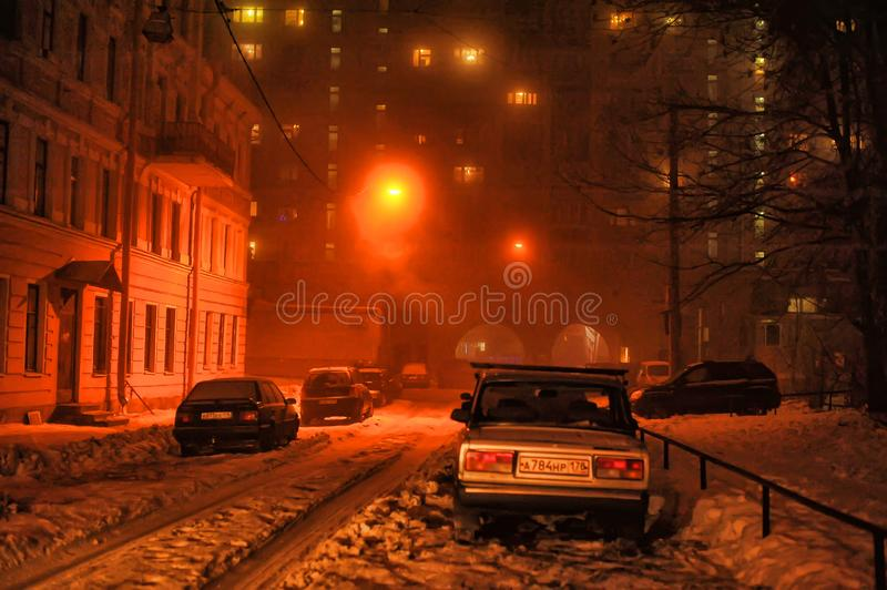 Cars parked on the street and the light of a lantern in winter stock photo