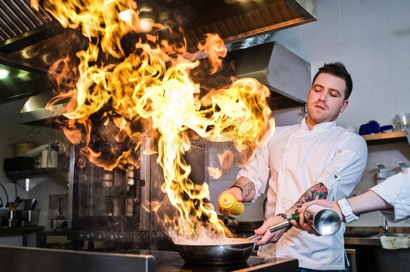 Russia, St. Petersburg, 03.17.2019 - chef is making flambe in a restaurant kitchen, dark background. stock photo