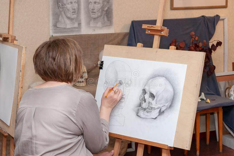 An adult female student sits at the easel, learning to draw. Russia, Surgut, October 17, 2018: Art Studio for adults named after V.Gorda. An adult female student stock image