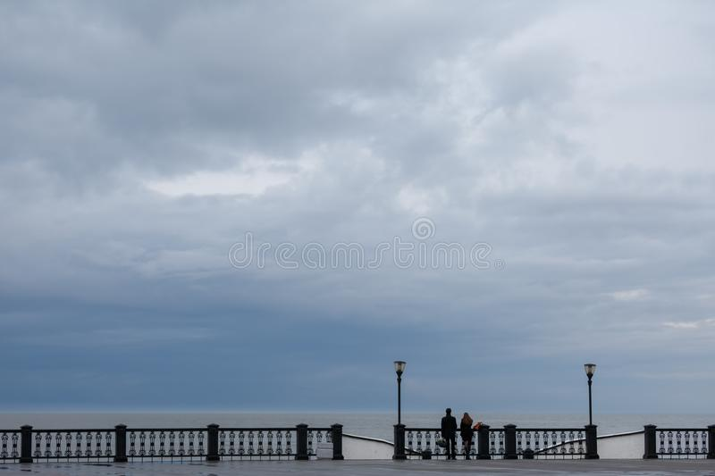 Young man and young woman stand around the openwork fence and look at the sea on a rainy day stock photography