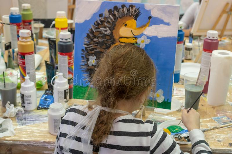 Russia, Tatarstan, April 20, 2019. The girl draws a hedgehog. Creative teen girl paitning a picture on easel. Interior of the art stock photo