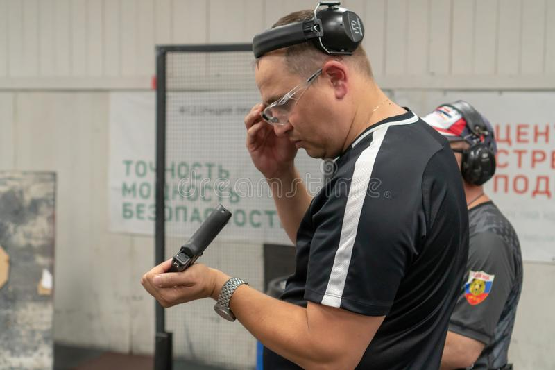 Russia, Tatarstan, June 23, 2019. Shooting training. The man shoots from the gun at the shooting range under the supervision of an stock photography