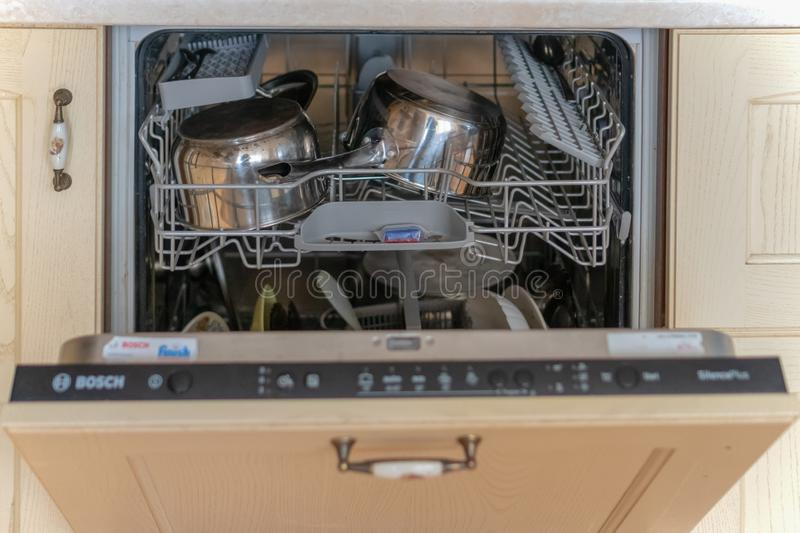 Russia, Tatarstan, May 31, 2019. Open dishwasher with dirty dishes royalty free stock photos