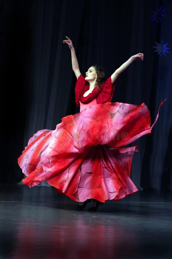 A girl in a lush red dress dancing dance of gypsy. stock images