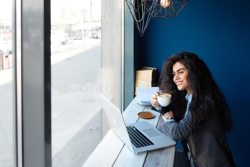 Russia - Tyumen 2017: Beautiful brunette sitting in coffee shop and working on computer. stock photos