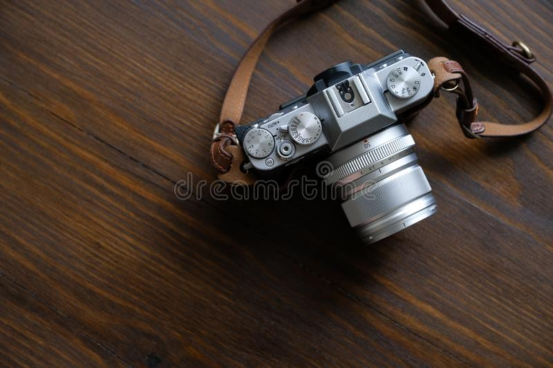 Russia, Tyumen, 12.05.2019. Vintage silver and black Fujifilm camera with brown leather strap on wooden table. Copy space for text royalty free stock photos