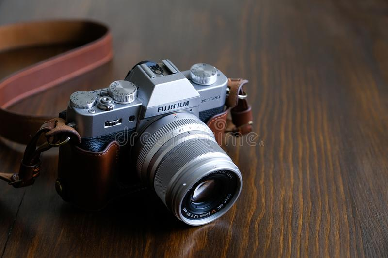 Russia, Tyumen, 12.05.2019. Vintage silver and black Fujifilm camera with brown leather strap on wooden table. Copy space for text stock photo