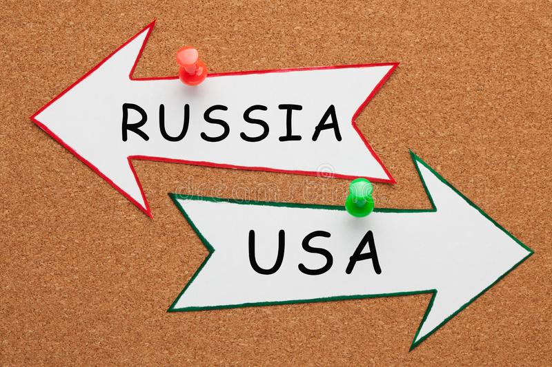 RUSSIA USA Concept. RUSSIA and USA words on paper arrow pinned on cork board. Business concept royalty free stock image