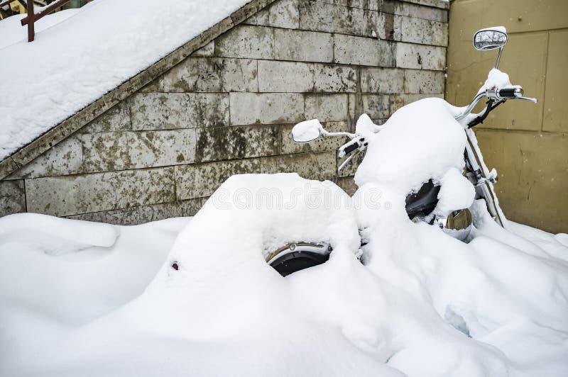 russia vinter Motorcykeln som parkeras nära väggen av huset, täckas nästan fullständigt med snö och den väntande på våren, arkivfoto