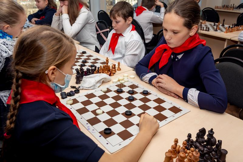 Russia, Vladivostok, 12/01/2018. Kids play chess during chess competition in chess club. Education, chess and mind games. stock photos