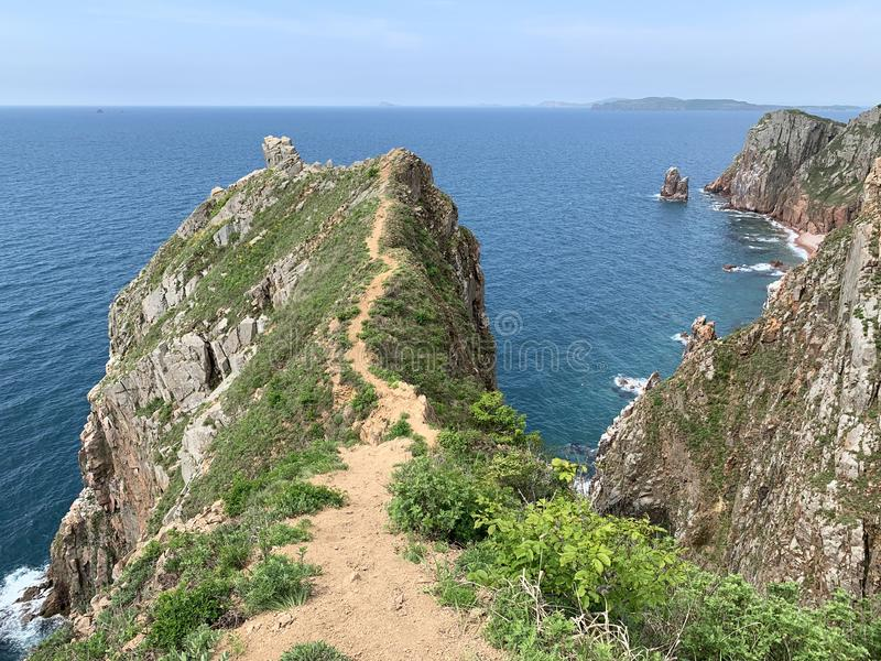 Russia, Vladivostok. The South-Eastern coast of the island of Shkot in summer. Narrow path along the crest of one of the rocky pro. Montories stock photography
