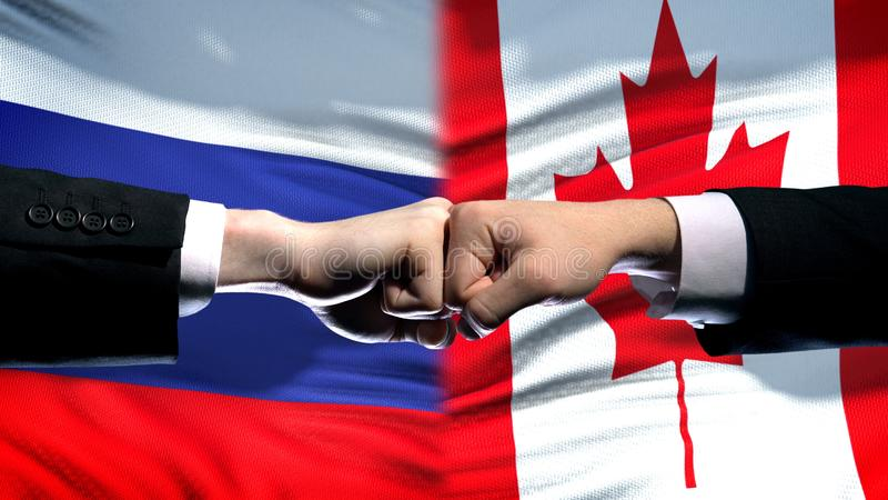 Russia vs Canada conflict, international relations, fists on flag background. Stock photo royalty free stock image