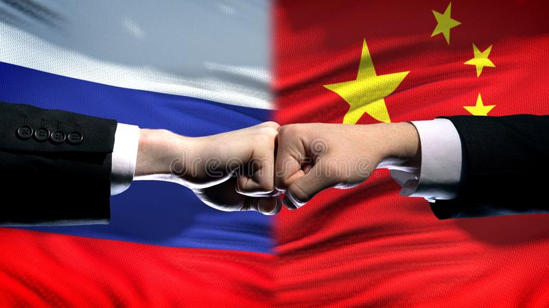 Russia vs China conflict, international relations, fists on flag background. Stock photo stock image