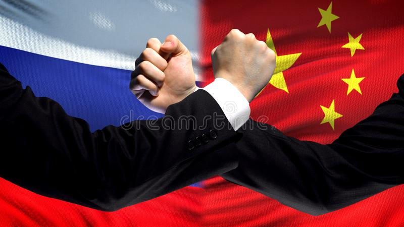 Russia vs China confrontation, countries disagreement, fists on flag background royalty free stock photography