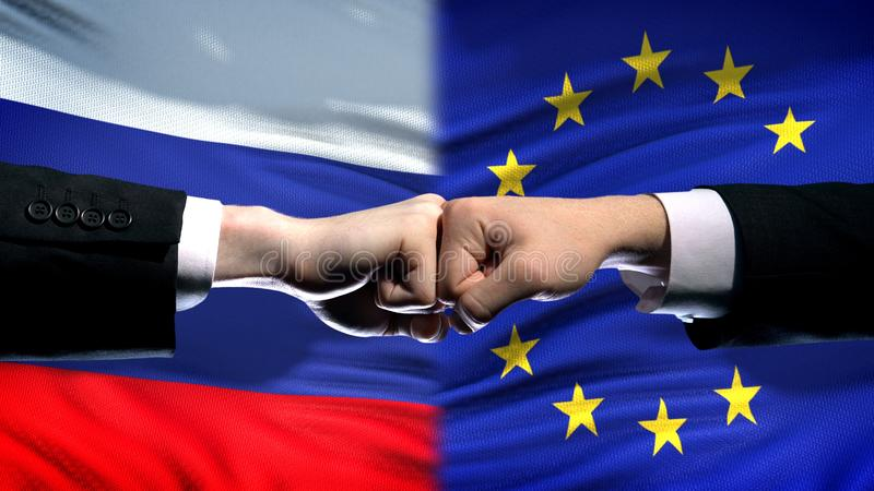 Russia vs EU conflict, international relations crisis, fists on flag background. Stock photo stock photography