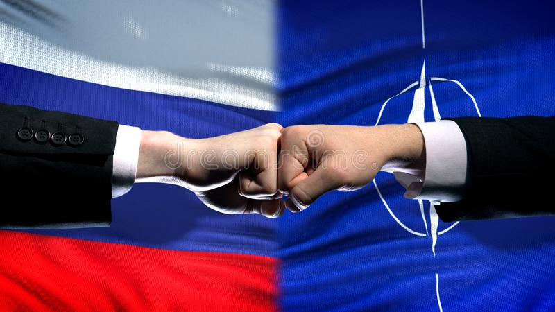 Russia vs NATO conflict, international relations, fists on flag background. Stock photo stock photo