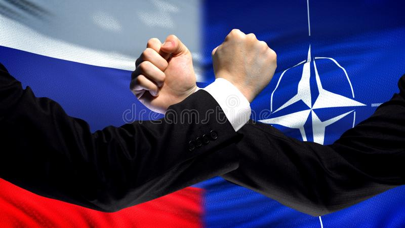 Russia vs NATO confrontation, countries disagreement, fists on flag background royalty free stock image