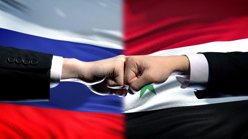Russia vs Syria conflict, international relations, fists on flag background. Stock photo stock photos