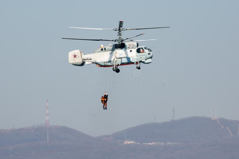 A Russian Air Force helicopter lifts a lifeguard from sea water near a large city stock image