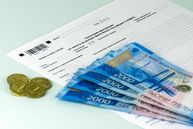Russian annual tax Declaration of taxes of individuals. The Form 3-NDFL. A few Russian notes and coins are on the sheet of the Dec stock photos