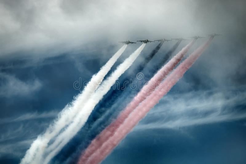 Russian attack aircraft SU-25, planes with colored contrail. Colors of Russian flag. Saint Petersburg, Russia - July 30, 2017: Su-25 aircraft NATO codification royalty free stock photo