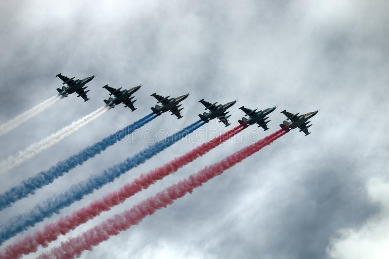 Russian attack aircraft SU-25, planes with colored contrail. Colors of Russian flag. Saint Petersburg, Russia - July 30, 2017: Su-25 aircraft NATO codification stock images
