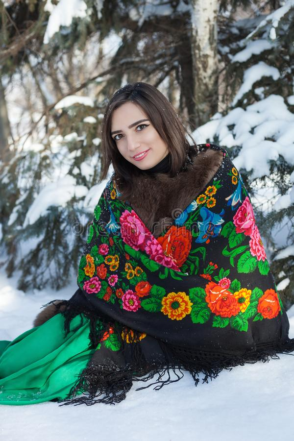 Russian beauty sits under a tree in a winter forest. stock photography