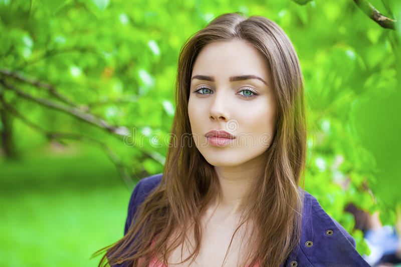 Russian beauty - Young brunette girl at a white birch. Close up, portrait of a young beautiful brunette girl on a background of leaves of a birch royalty free stock images