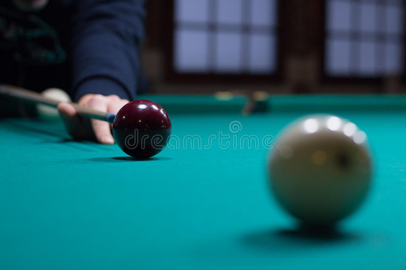 Russian billiards player aims to shoot red ball with cue stock photos