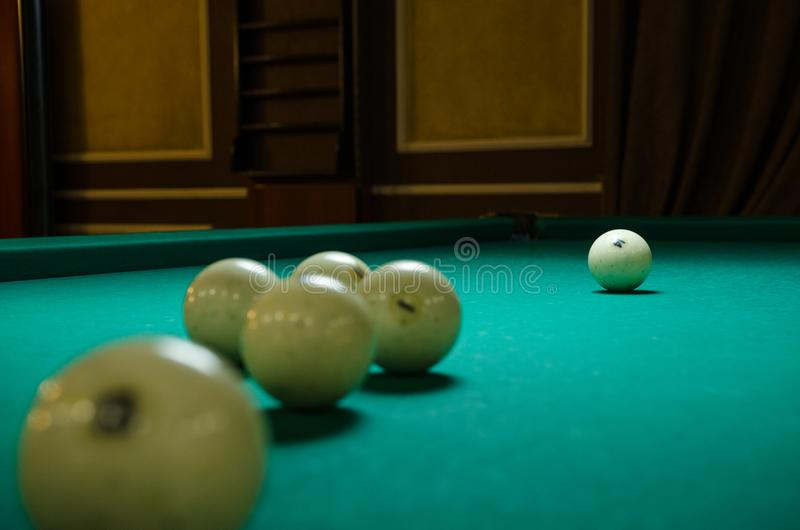 Russian billiards white balls, yellow cue ball, wooden cue on a large table with green cloth stock image