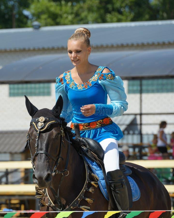 Russian championship in trick riding. Lytkarino, Moscow region, Russia - July 12, 2014: Alexandra Kalinina warms up her horse during Russian championship in royalty free stock photos