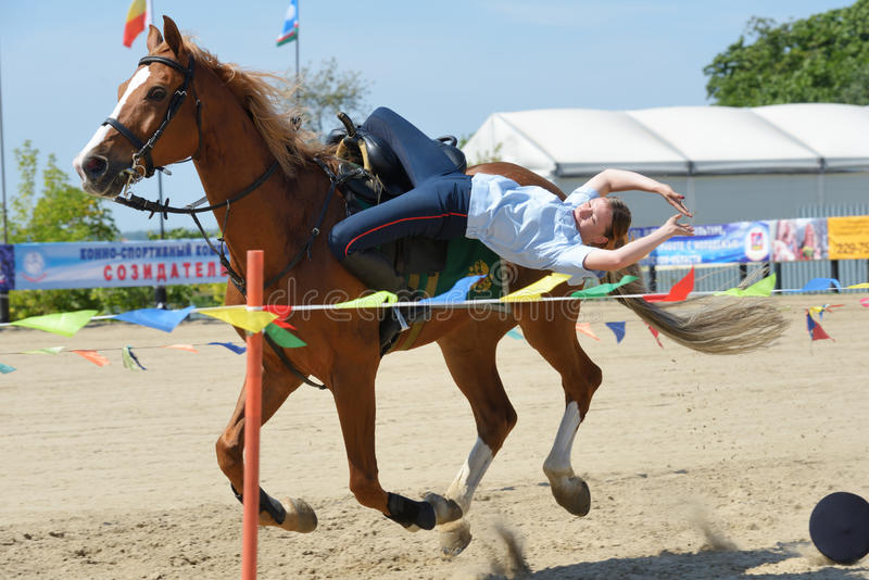 Russian championship in trick riding. Lytkarino, Moscow region, Russia - July 12, 2014: Julia Lysenko from Moscow police performs stunts during Russian stock image