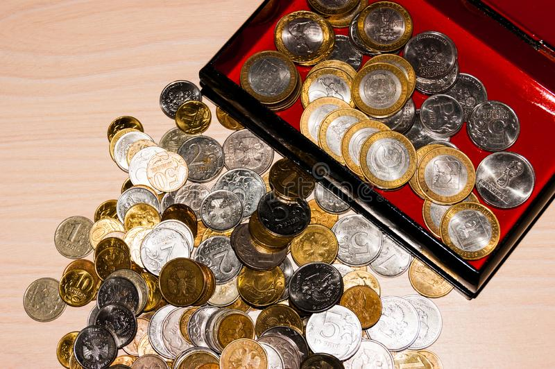 Russian coins of different denominations lie in a heap on the table, next to a casket with coins. Russian coins of different denominations lie in a heap on the royalty free stock photography