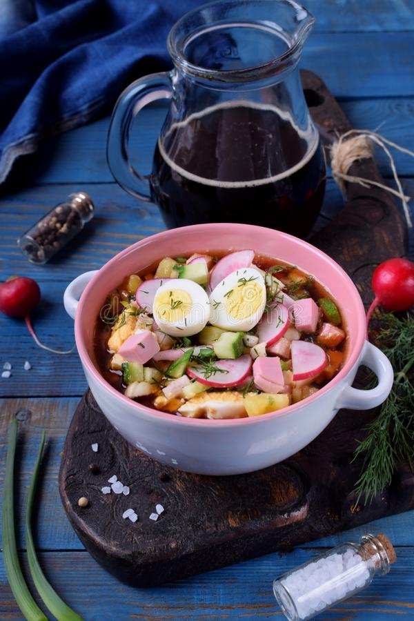 Russian cold soup Okroshka with vegetables, sausage, eggs and kvass in a ceramic bowl. On the blue table stock photo