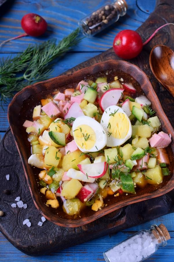 Russian cold soup Okroshka with vegetables, sausage, eggs and kvass. In a bowl on the blue table royalty free stock photo