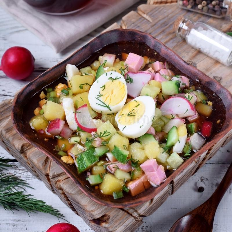 Russian cold soup Okroshka with vegetables, sausage, eggs and kvass. In a wooden bowl on the white table stock image